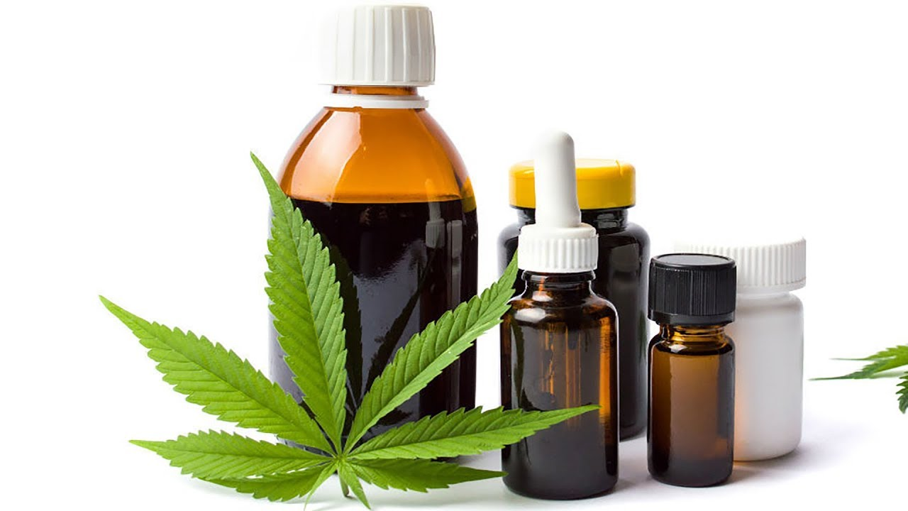 a group of cannabis oil products on a table with a leaf in front of them